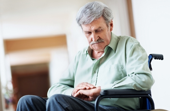 Sad old man sitting on a wheelchair in the hospital